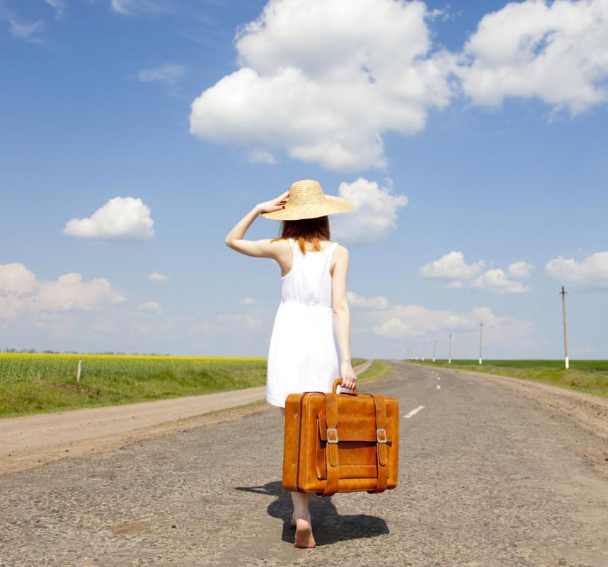 Donna con valigia per le vacanza al mare
